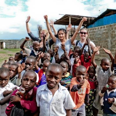 Adolescentes se toman fotos junto a niños en un descanso de su trabajo voluntario.